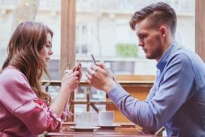 always connected, internet addiction, young couple in cafe looking at their smartphones, social network concept