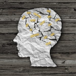 Brain disease therapy and mental health treatment concept as a sheet of torn crumpled white paper taped together shaped as a side profile of a human face on wood as a symbol for neurology surgery and medicine or psychological help.