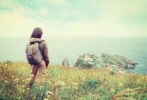 Traveler young woman standing on hill and looking to the town on peninsula. Image with instagram filter